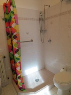 bagno in camera con doccia e lavatrice