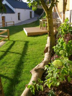 Level lawn and decking enclosed by stock proof fencing.