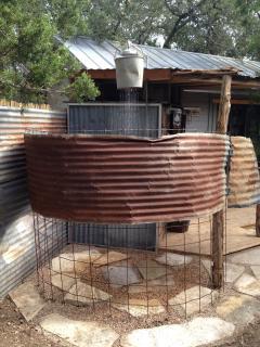 Outdor shower with rusty bucket rain head.