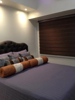 Custom made privacy blinds in decorative color with pin lights above headboard