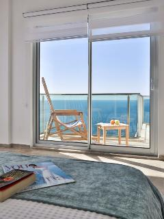 Twin bedroom with balcony and sea views.