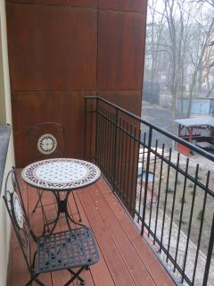 Apart 1- balcony with a stylish coffee table and chairs overlooking a courtyard and a small park