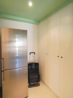 there is a big fridge with freezer and the trolley for the shopping
