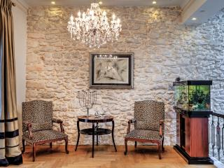 Part of the living area with a wonderful aquarium high ceiling and antique stone walls.