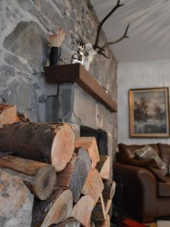 West Lodge lounge with lovely cozy log burner and feature stone wall.