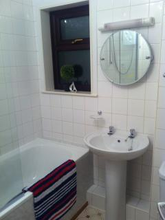 BATHROOM WITH MODERN WHITE SUITE,    LARGE MIRROR,    SHOWER OVER BATH,  SHOWER SCREEN