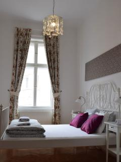 Comfortable ensuite 'white' bedroom with art glass chandelier and wardrobe