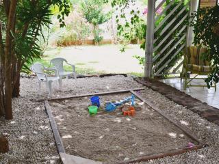 Un bac à sable pour les enfants dans un coin ombragé du jardin sous les yeux des parents - Sandbox
