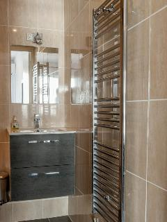 entirely tiled bathroom with hairdryer and towel heater stand