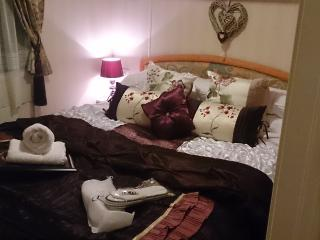 Main Bedroom- with crisp white bed linen, memory foam topper, mini toiletries heating  hotel slipper