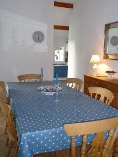 There is a dining table and 6 chairs. Sideboard with crockery  Patio doors (with electric shutters).
