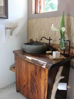 Powder room natural styling with stone basin and hand chosen drift wood fixtures.