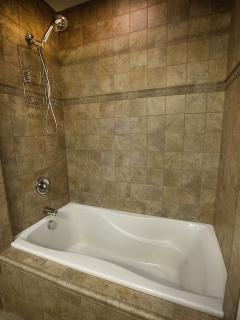 Italian ceramic tile surrounds a deep soaking tub and shower.