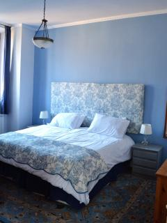 The bedroom with king size bed or twin beds has wardrobe and drawer storage.