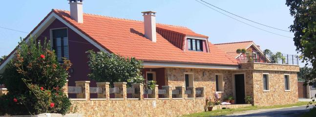 Fachada de la casa, con un bonito jardín con piscina y terraza