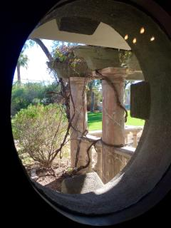One of many round windows looking out to the patio and trellis area