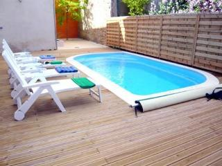The private swimming pool with decked surround and sun loungers