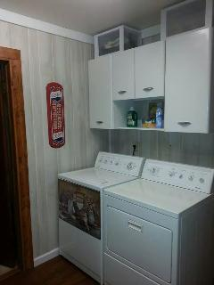 Laundry room also has a laundry tub and dryer with shoe rack.