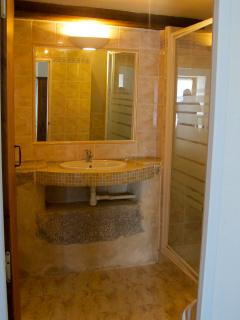 Ensuite bathroom with exposed stone as well as sleek modern fittings and powerful shower..