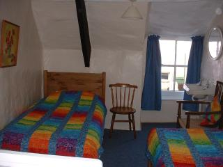 The twin bedroom with it's old wooden beams, sloping ceiling and colourful quilts.