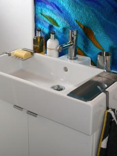 Bathroom, with more original artwork, has a toilet, sink and shower. Quality toiletries provided.
