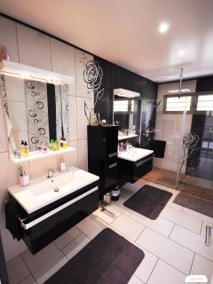 The bathroom with a large shower and double vanity sinks