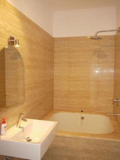 Ensuite bathroom with bath and shower off the second bedroom