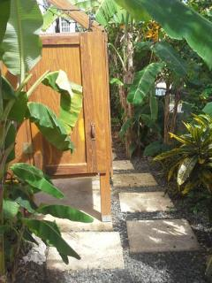 The outdoor shower is surrounded by banana trees.