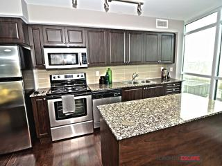 Open concept living, dining and kitchen area with floor to ceiling windows and breakfast bar