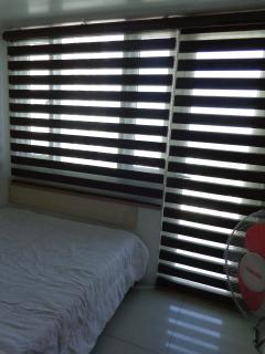 The bedroom with an elegant blinds to control the flow of sunlight in the unit