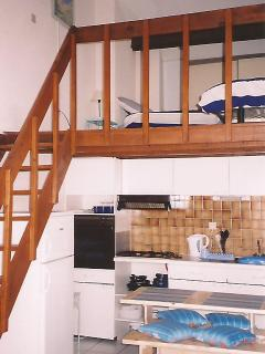 Stairs to mezzanine with two single beds. (There is a double bed in the main bedroom)