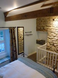 The bedroom is open plan with stone walls and vaulted ceilings.