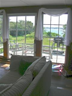 View from sitting room, across deck: grass, picnic table (+now a larger gas grill) to cove.