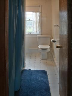 Bathroom has Bathfitter tub/shower with curved rod. Multiple towel racks.