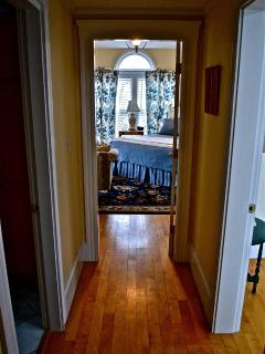 Hallway showing 2 bedrooms with private spa bath. Hardwood floor throughout.