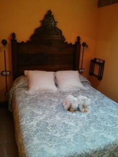 Habitación con cama doble, y cabezal antiguo