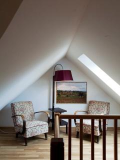 Cozy reading corner under a mansard roof.