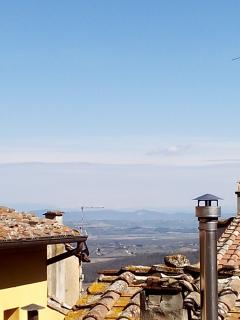 Partial view from window on old roofs and Val di Chiana, mountains and lake