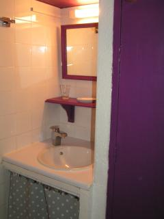 Le lavabo de la salle de bain et porte wc à droite