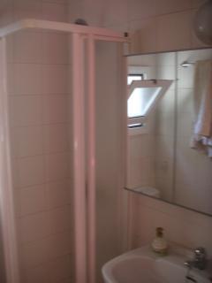 Baño con ducha y mueble con espejo