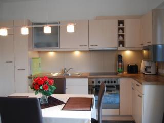 Küche mit Herd, Spülmaschine, Kühlschrank, Toaster, Kaffeemaschine und Essbereich