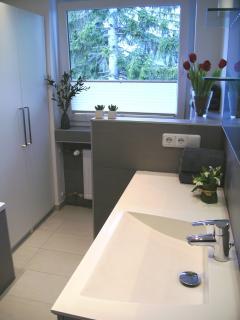 Badezimmer mit großem Waschtisch, WC getrennt durch Schamwand, Schrank, Wanne und Dusche, Fön