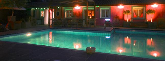 la nuit, la piscine et la terrasse illuminées