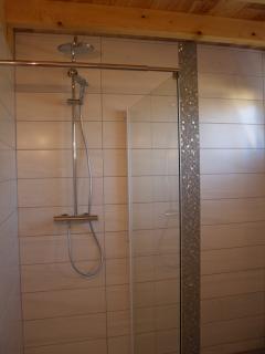 douche à l'italienne spacieuse, avec paroi en verre.
