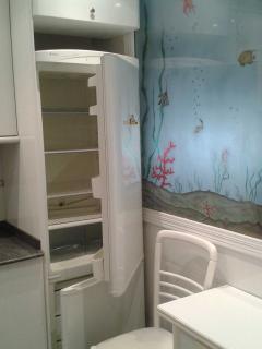 Frigorifico con congelador y mesa de cocina con dos sillas.