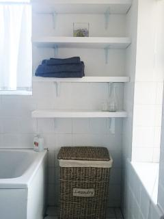 Family bathroom with shelving for toiletries, towels, etc