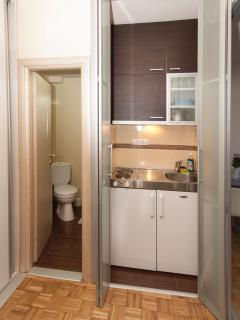 Fully equipped kitchen with fridge, cooking items and stove, separated by a glass folding door