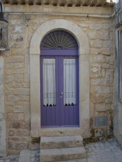 esterno particolare muro in  pietra e porta colore 'lilla'