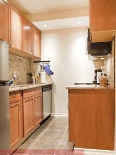 Separate kitchen with wood cabinetry, granite counter tops and stone back splash.  Dishwasher