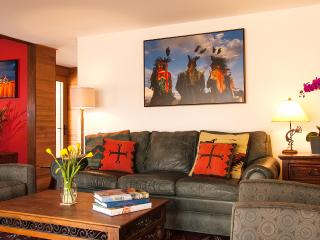 The living room is spacious and open with a great view of Taos Mountain.